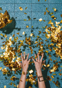 Hands of unrecognisable woman throwing golden confetti.